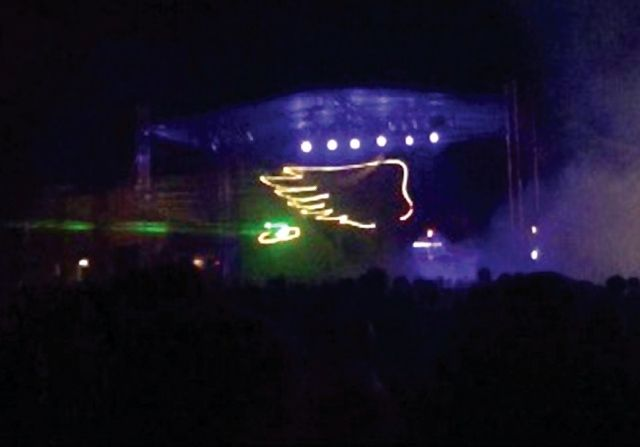 "The ""electric wing"" DeKalb Seed logo glows above the traditional ""winged ear"" DeKalb logo during a laser light show at DeKalb Cornfest 2013. This year's Cornfest was one of the venues at which DeKalb Seed unveiled the new branding and logo, which will be a complement to the well-known ""winged ear."""