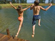 Boy and girl jumping in lake