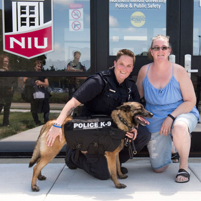 NIU Police Officer EB Slouka and Julie Castile celebrate K-9 Miley's new bullet/stab-proof vest.